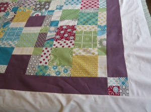 Here is the border with a 4 square in the corner. I chose the eggplant color because I thought that fit Jaki's personality and the quilt itself better than any other color in the quilt.